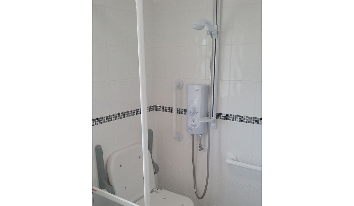 A white tiled bathroom that has had a new shower seat and handrails fitted to improve accessibility.